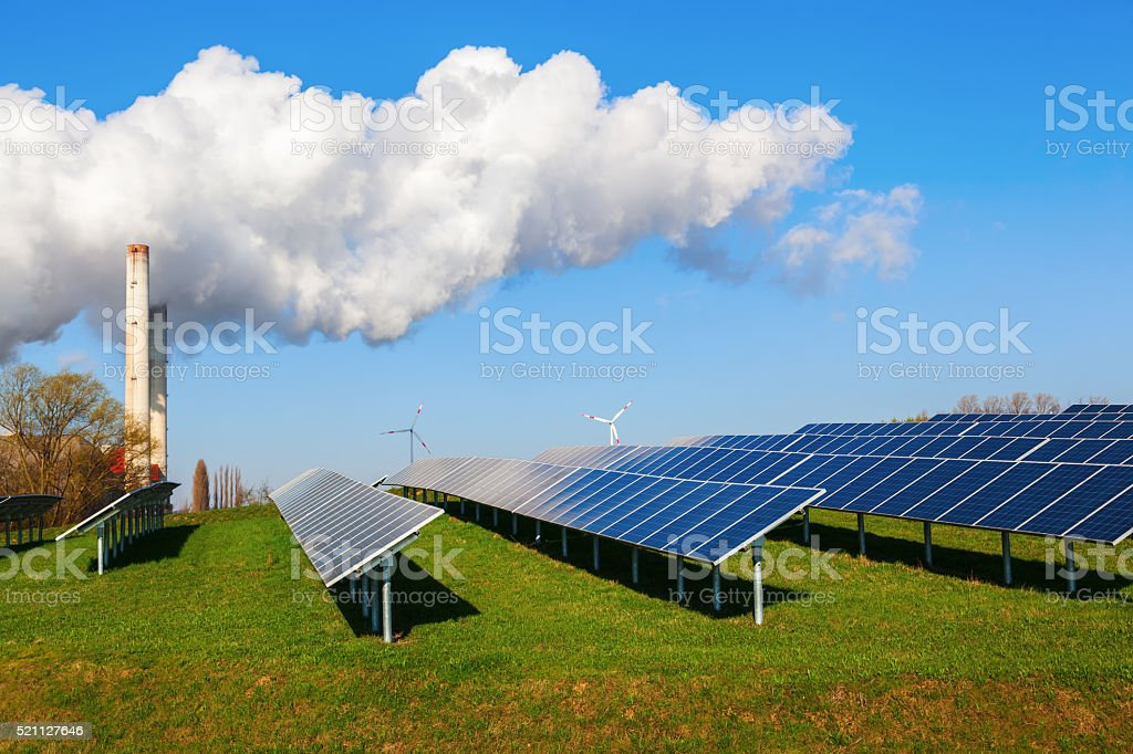 solar collectors and fossil-fuel power station stock photo