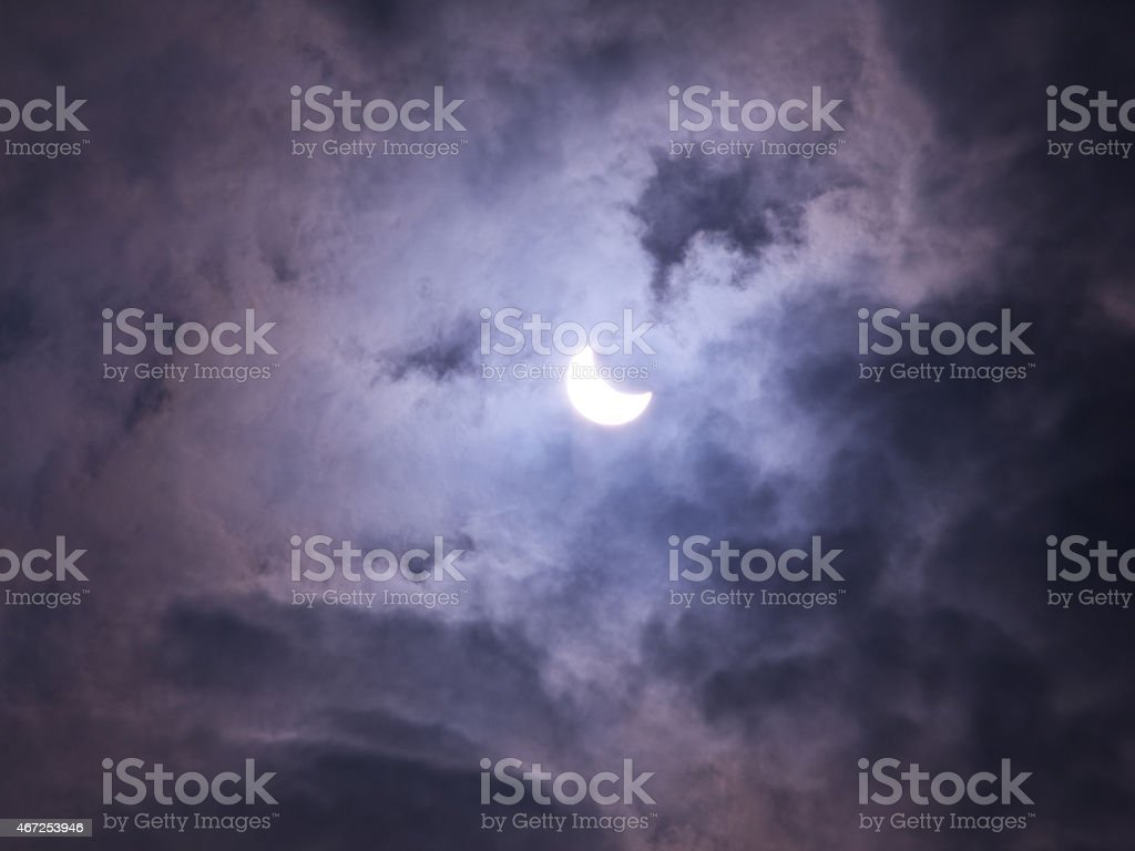 Solar eclipse 2015 in cloudy skies stock photo