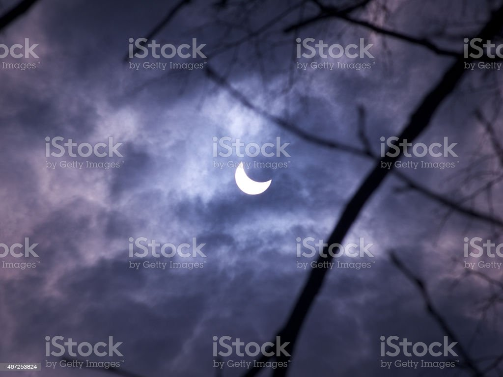 Solar eclipse 2015 in cloudy skies trough the trees stock photo