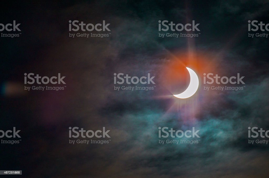 Solar Eclipse 2015 with clouds and charming glare stock photo