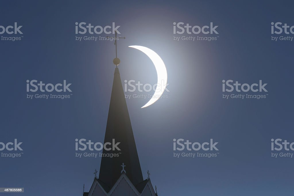Solar eclipse and church tower with cross on top stock photo