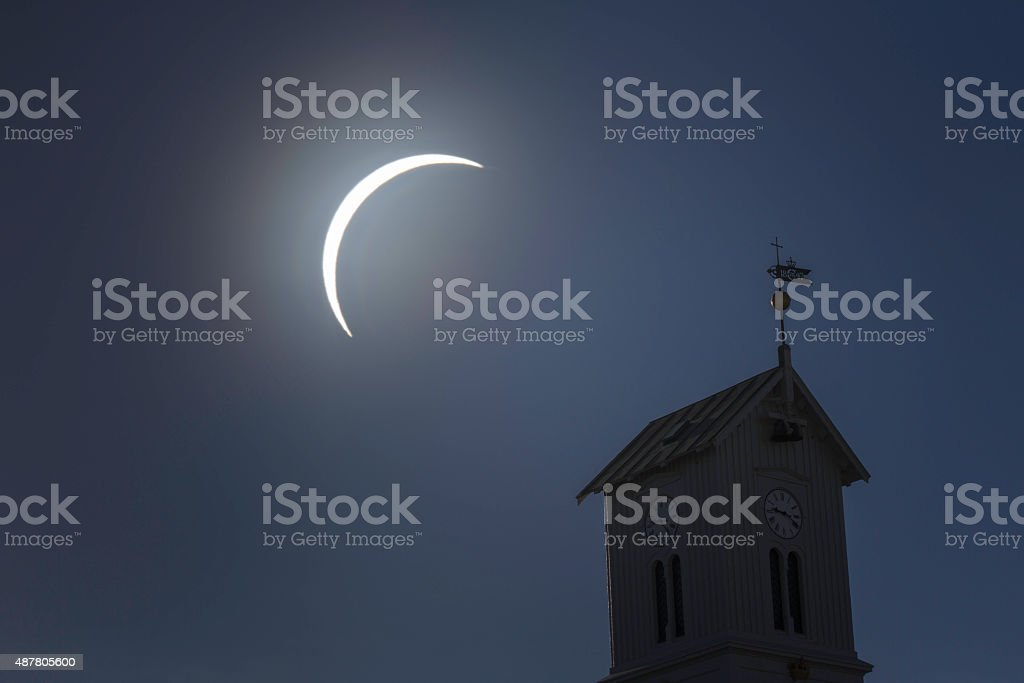 Solar eclipse and old church tower with clock in foreground stock photo