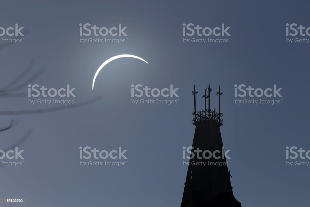Solar eclipse and rooftop with branches in foreground stock photo
