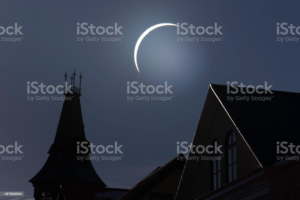 Solar eclipse seen over silhouette rooftops stock photo