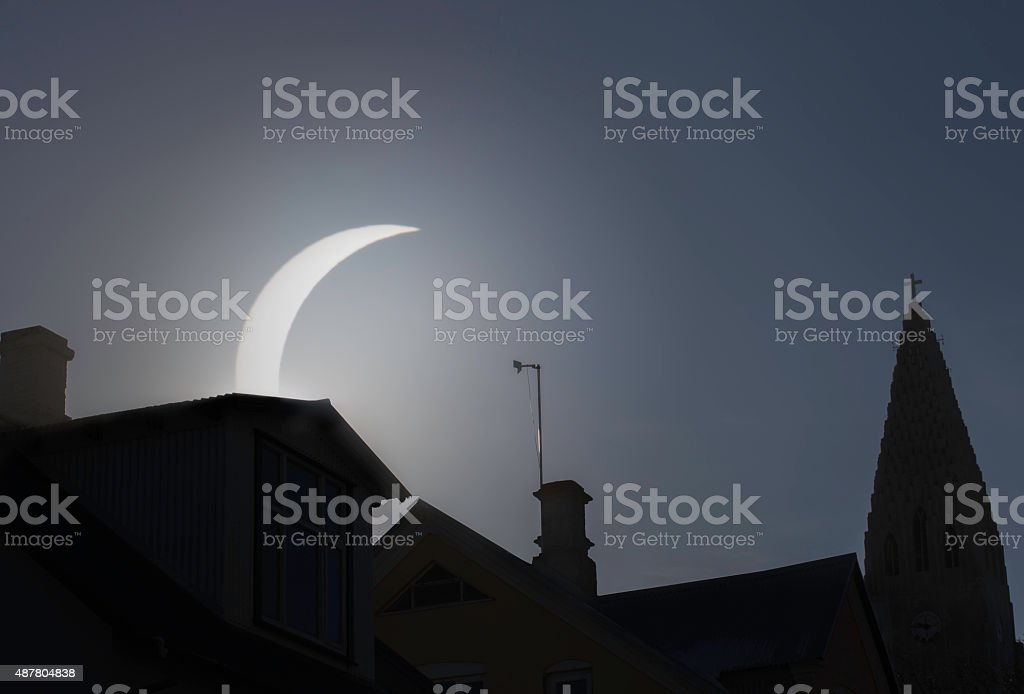 Solar eclipse seen with cityscape in foreground stock photo