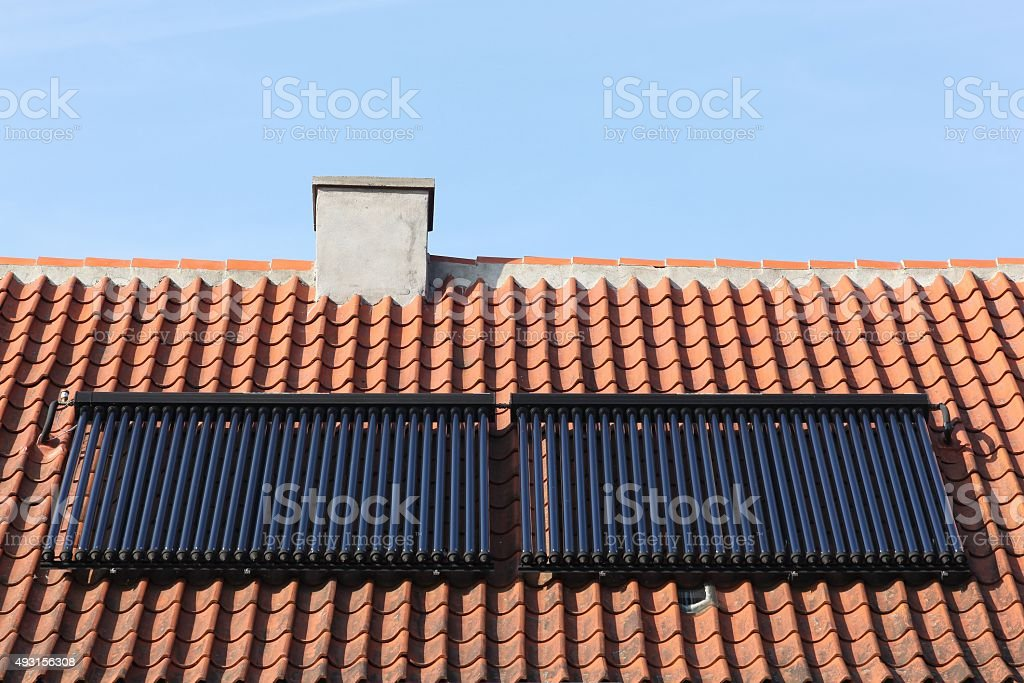 Solar glass tube hot water panel array on a roof stock photo