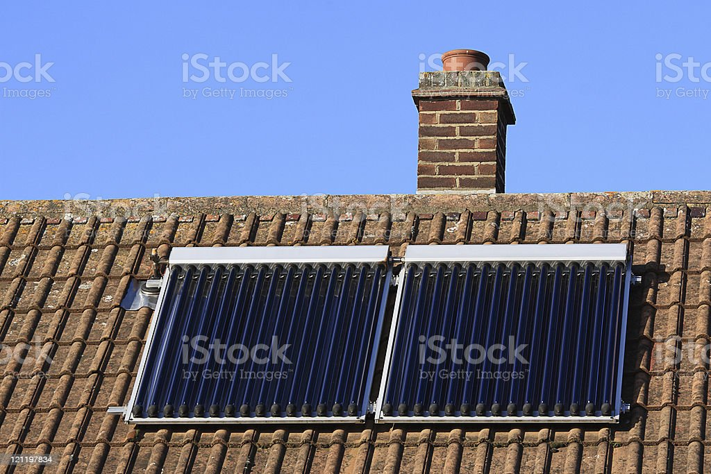 Solar heating panels on tiled house roof royalty-free stock photo