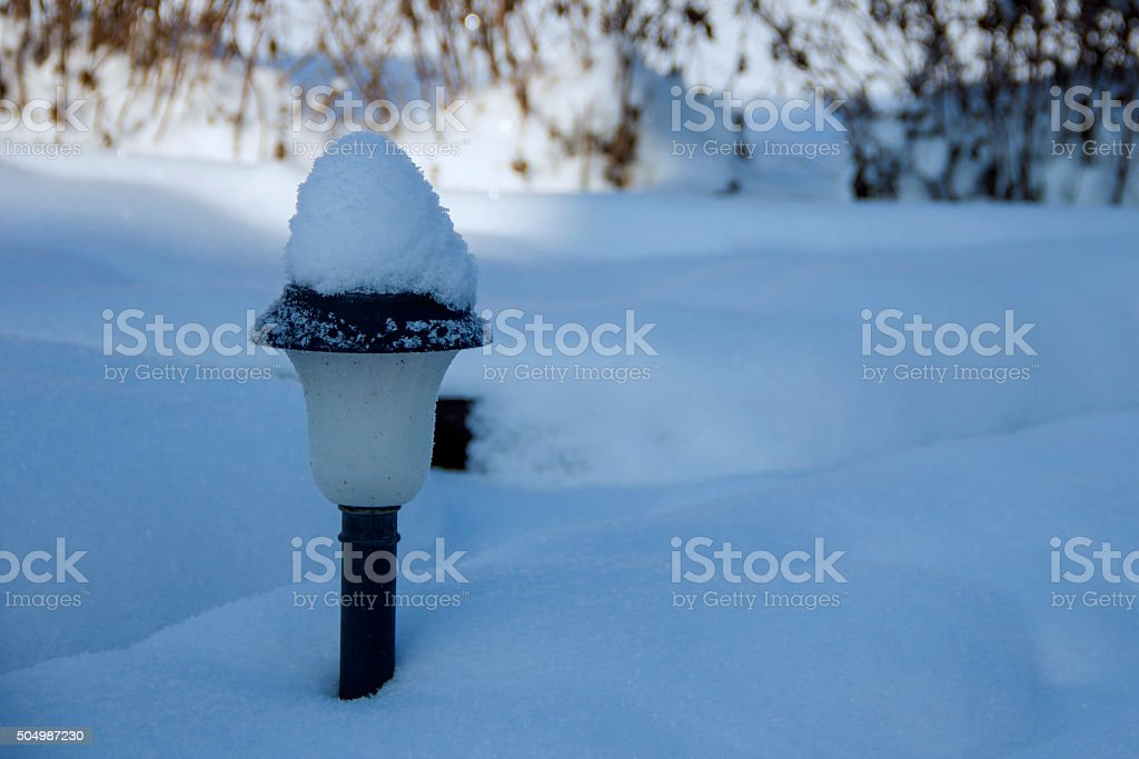 Solar Lantern in the winter garden in the middle of snow stock photo