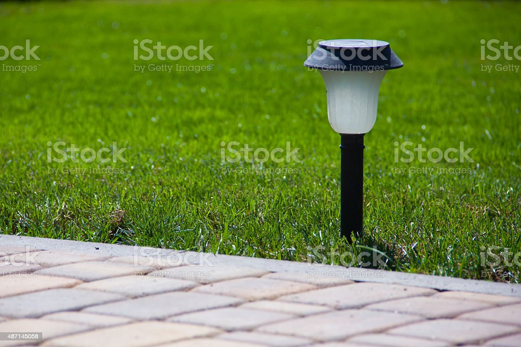 Solar Lantern near a paved garden path stock photo