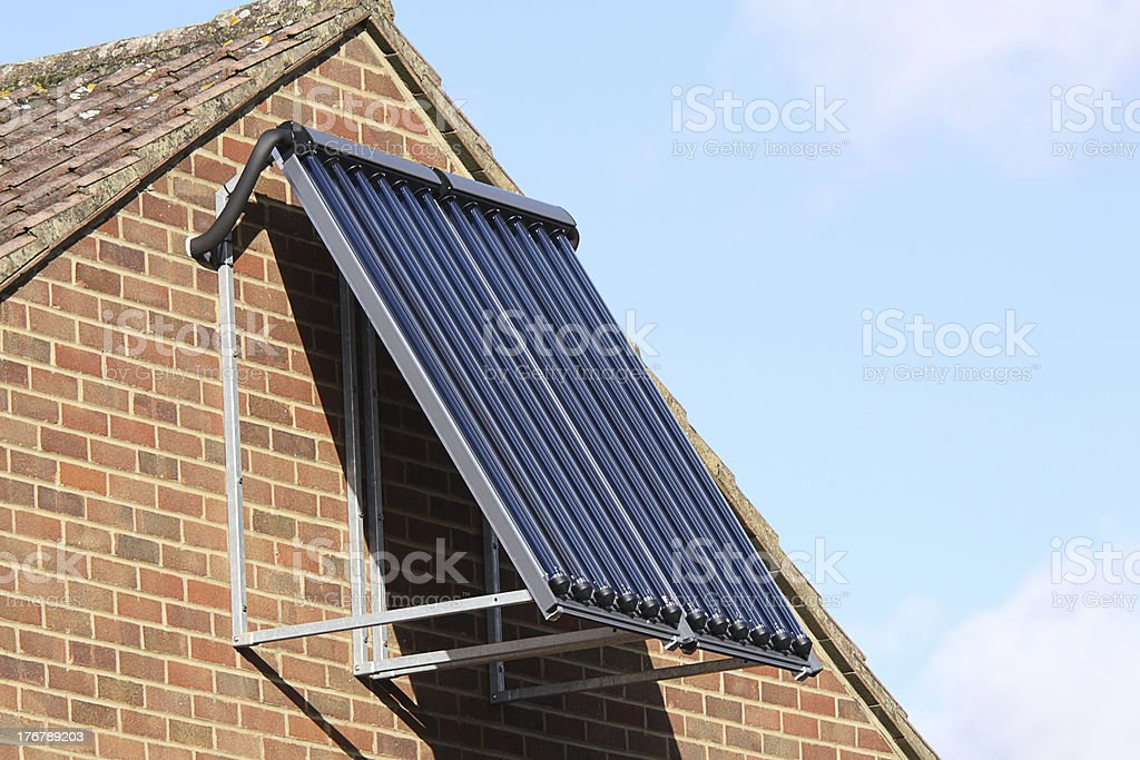 Solar panel heating water on domestic house wall royalty-free stock photo