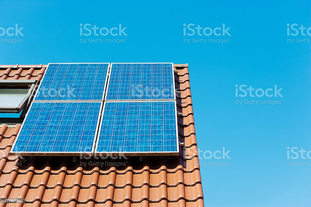 Solar panel on german rooftop against clear blue sky stock photo