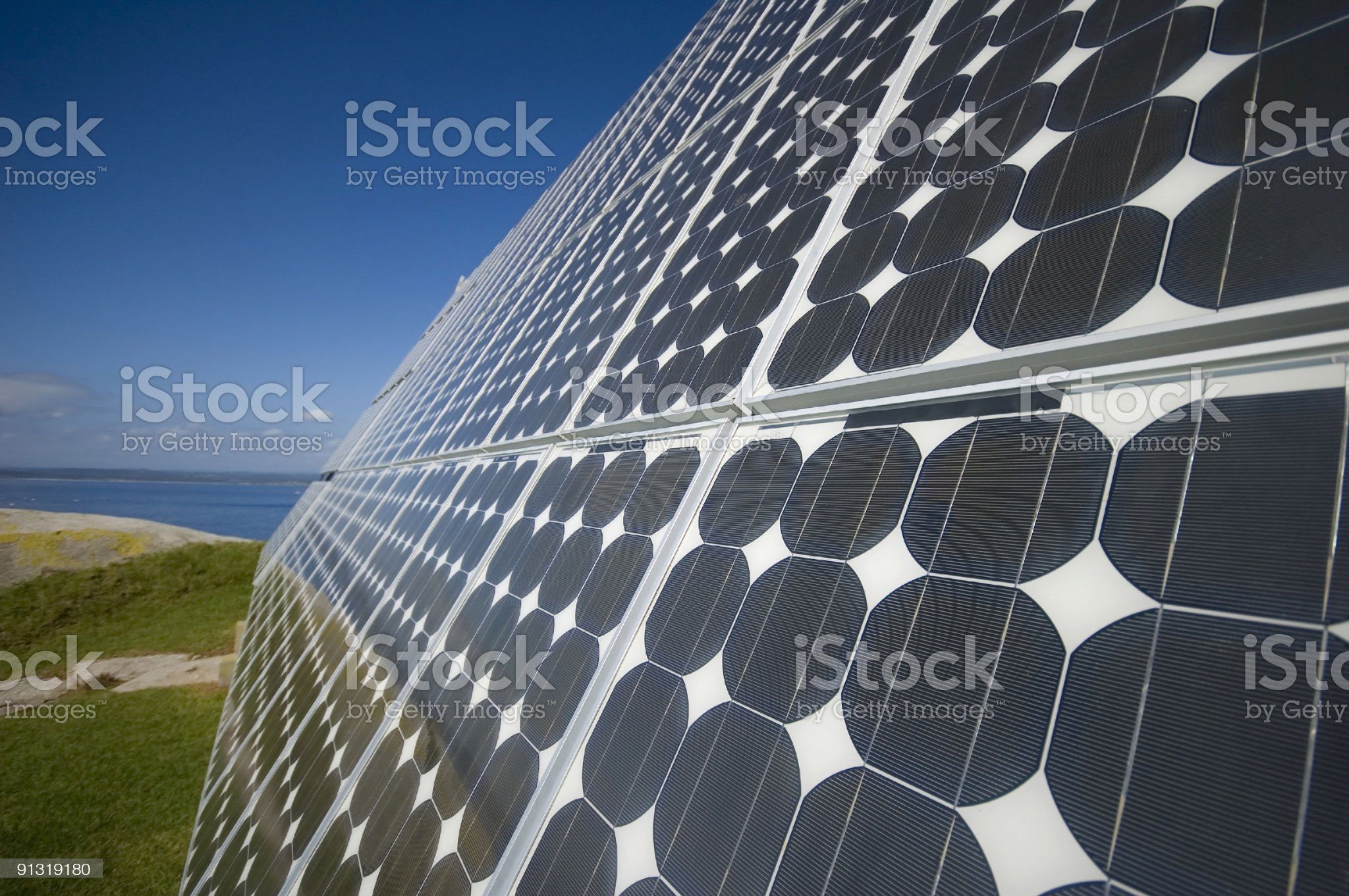 A solar panel with land and water in the background  royalty-free stock photo
