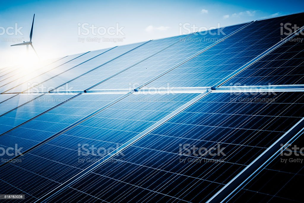 solar panels aginst sunshine and blue sky stock photo