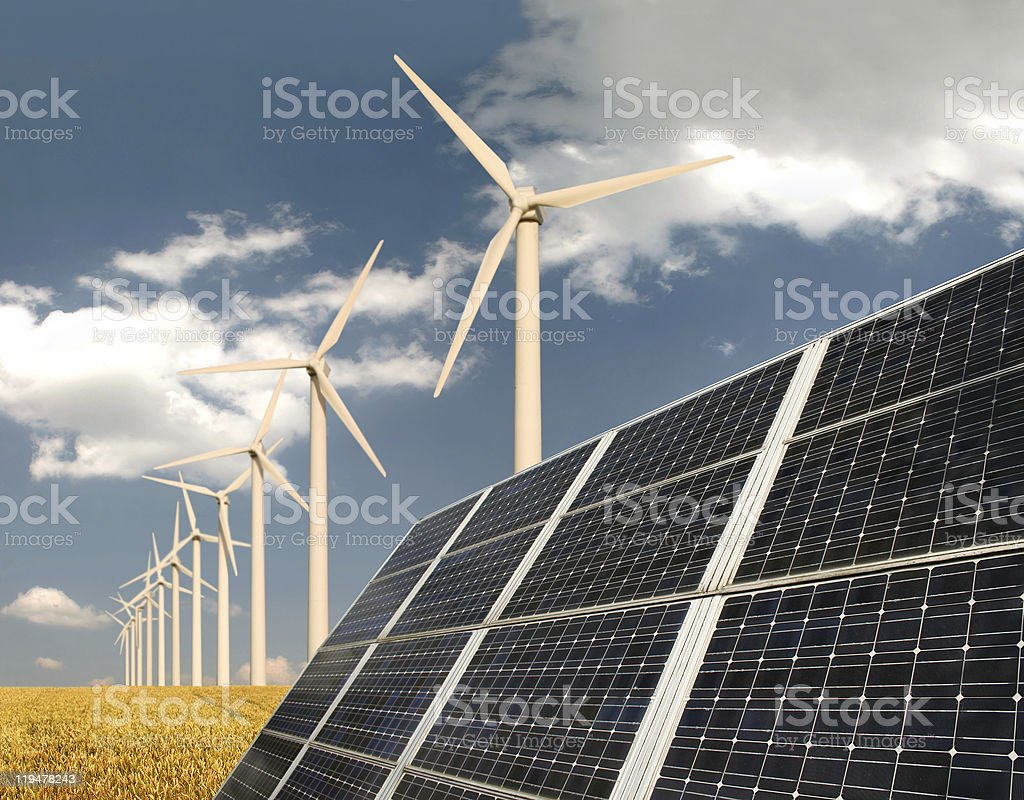 Solar panels and wind energy plants on a field stock photo