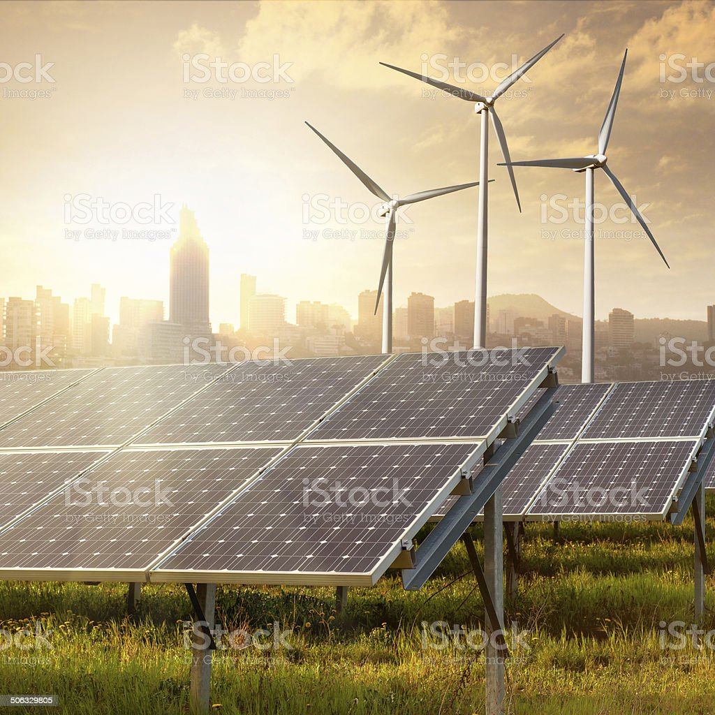 solar panels and wind generators against city silhouette on sunset stock photo