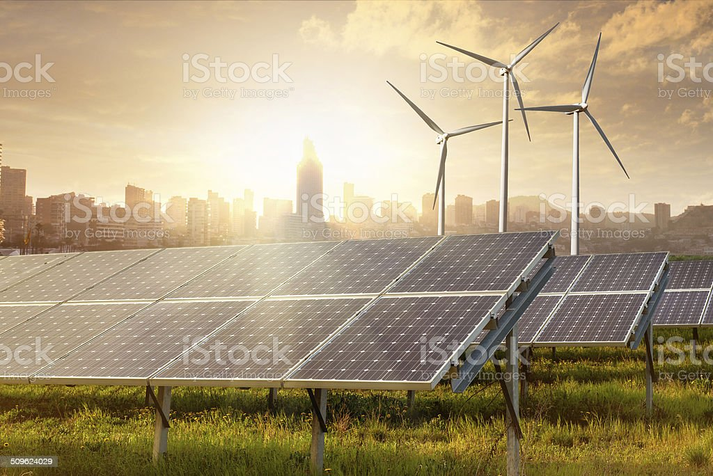 solar panels and wind generators against city view stock photo
