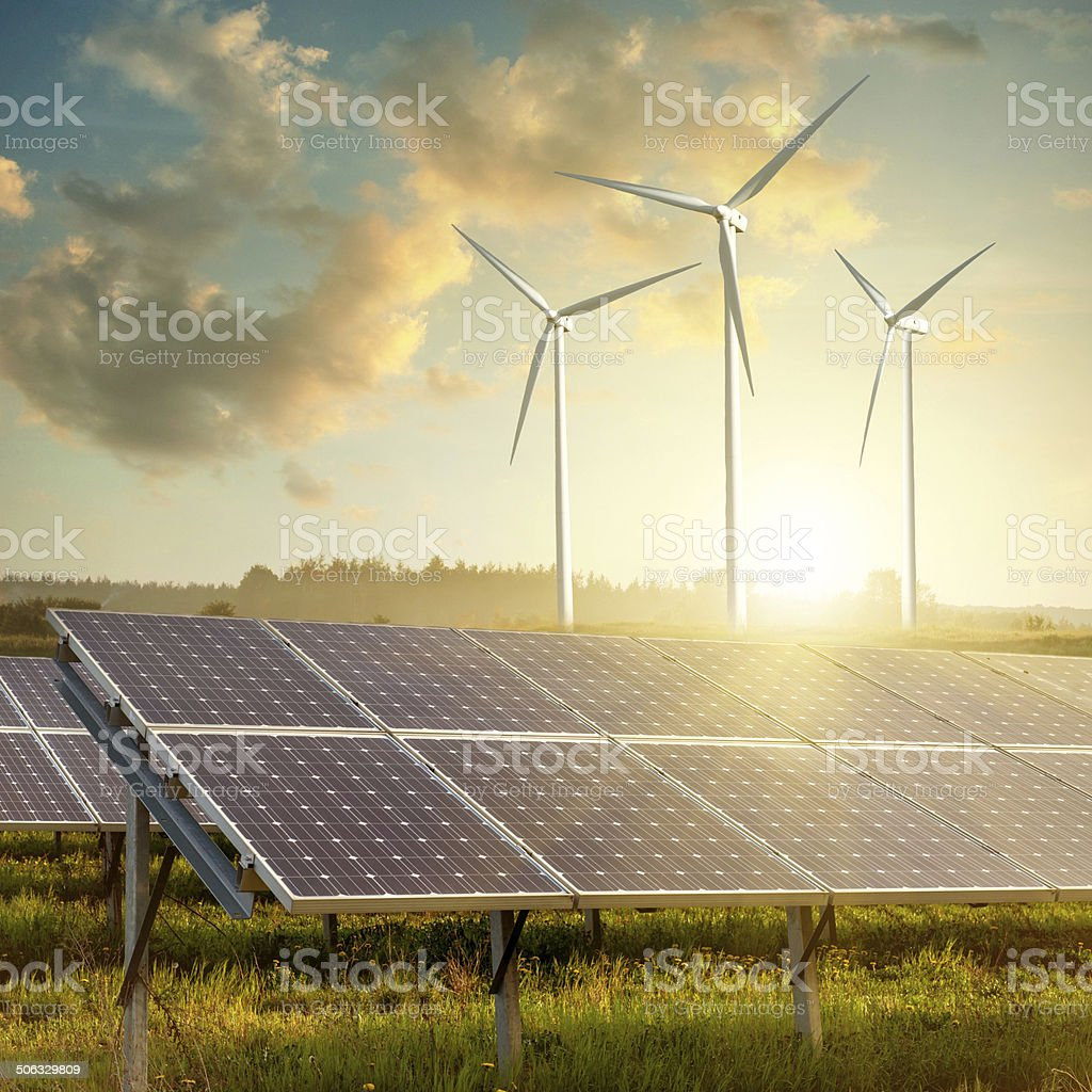 solar panels and wind generators against on sunset stock photo