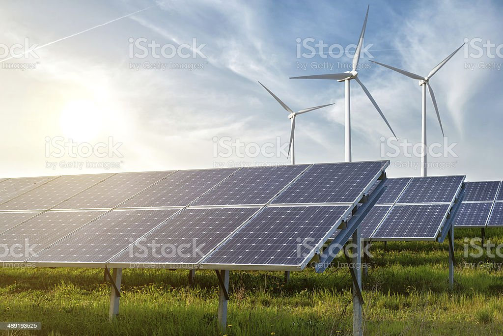 solar panels and wind generators under blue sky on sunset stock photo