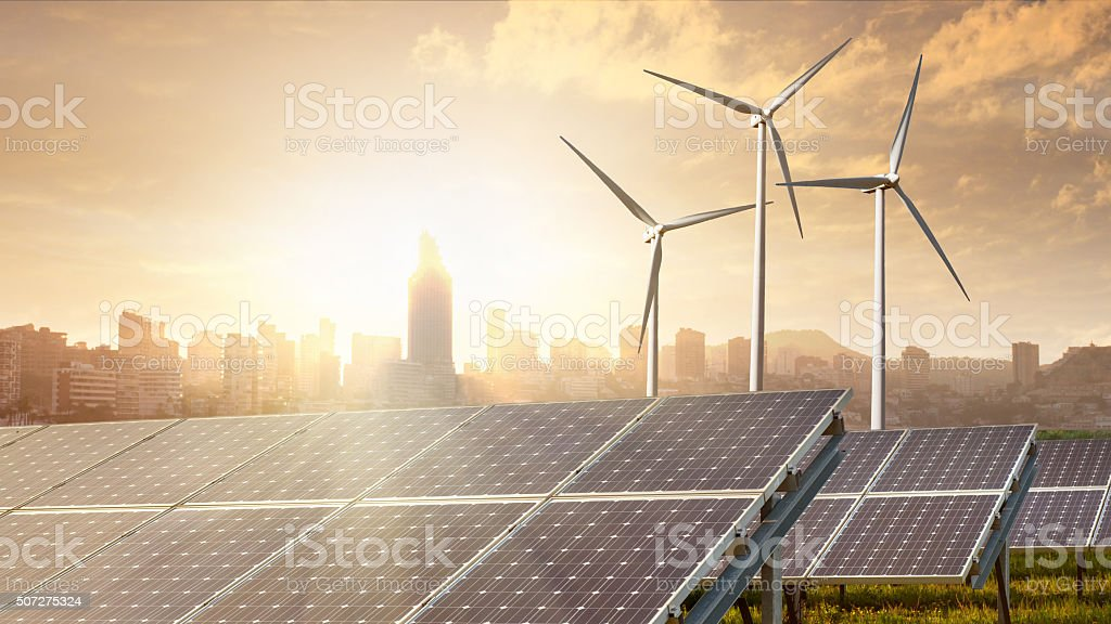 solar panels and wind generators under sunset and city stock photo