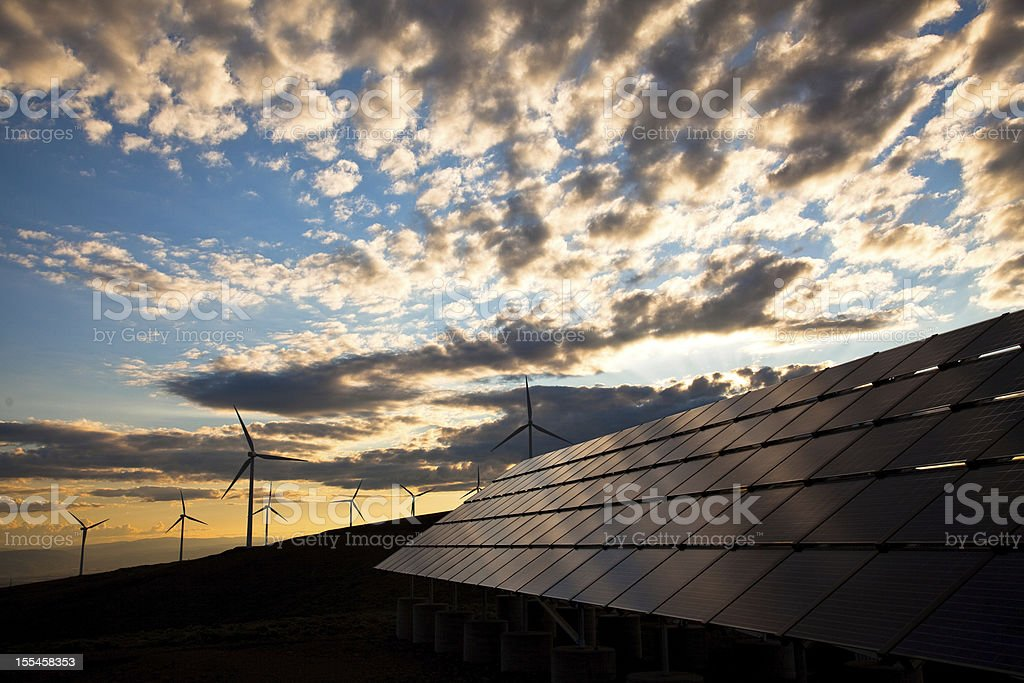 solar panels and wind turbines at sunset stock photo