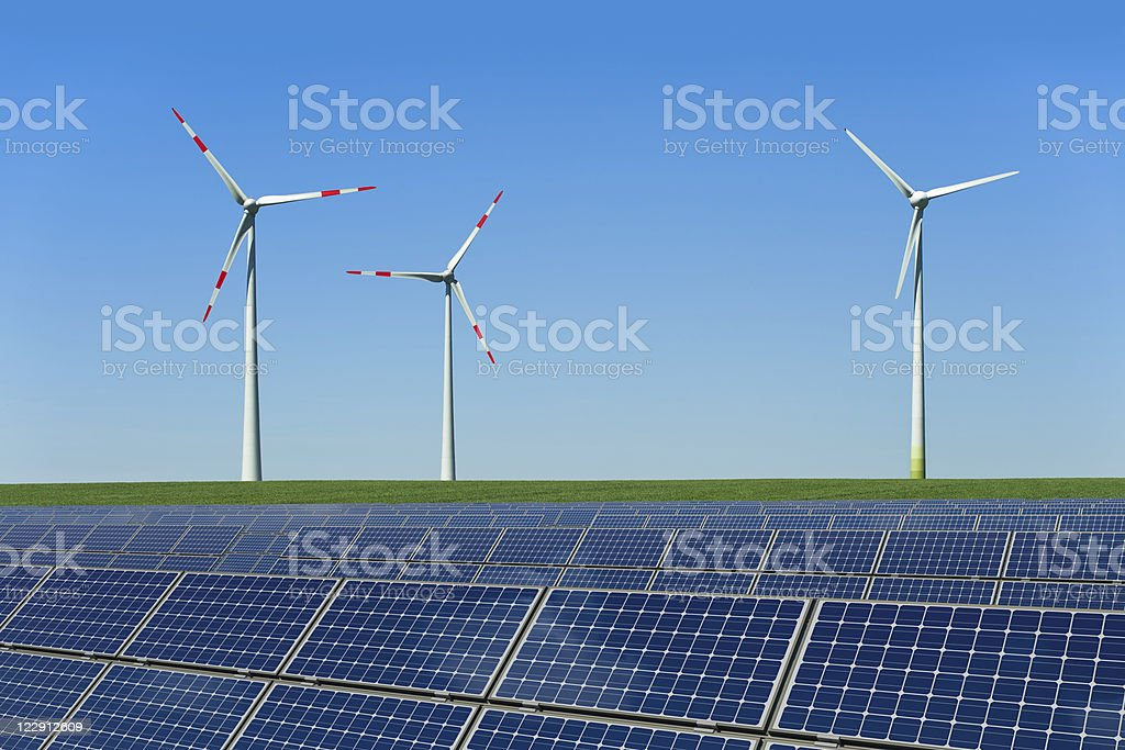 Solar panels and wind turbines in a field stock photo