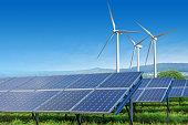 solar panels and wind turbines under blue sky
