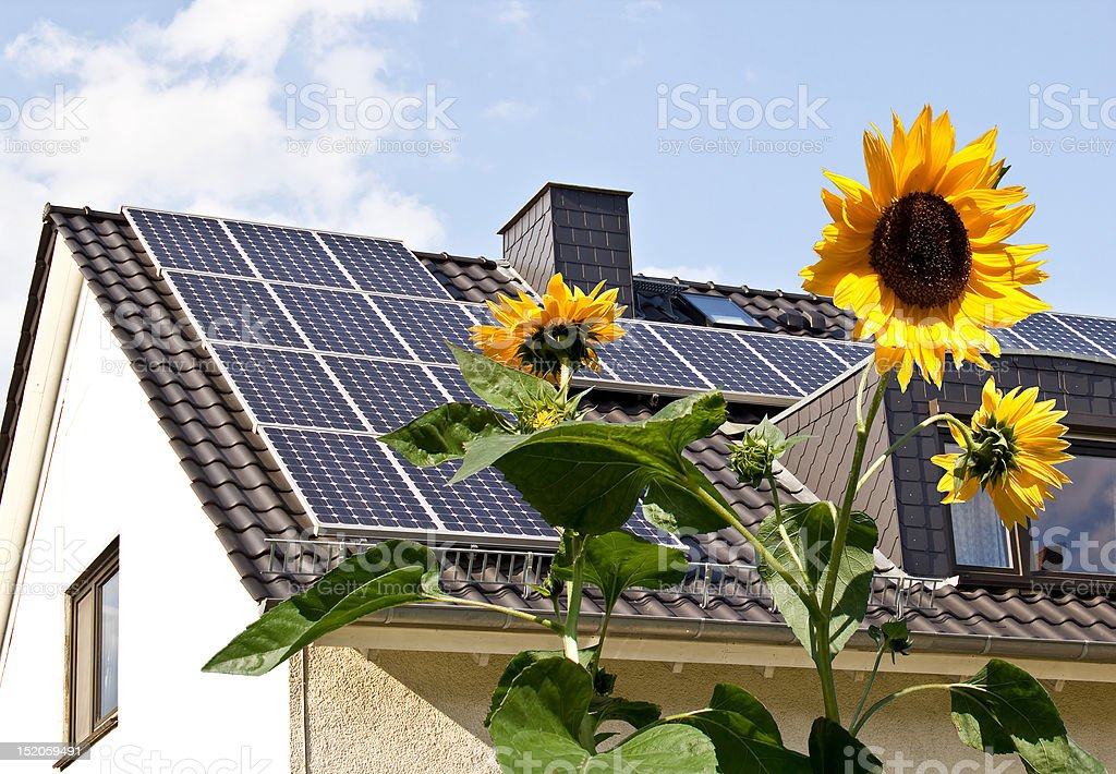 Solar panels at a roof with sun flowers stock photo