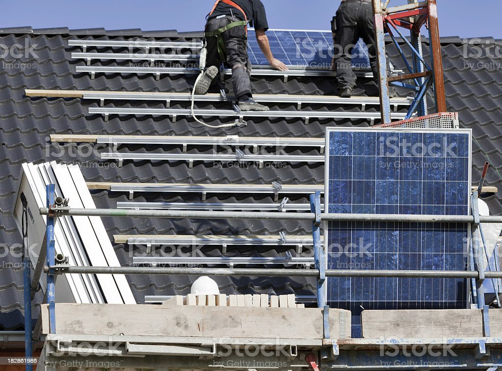 Solar panels being mounted on roof royalty-free stock photo