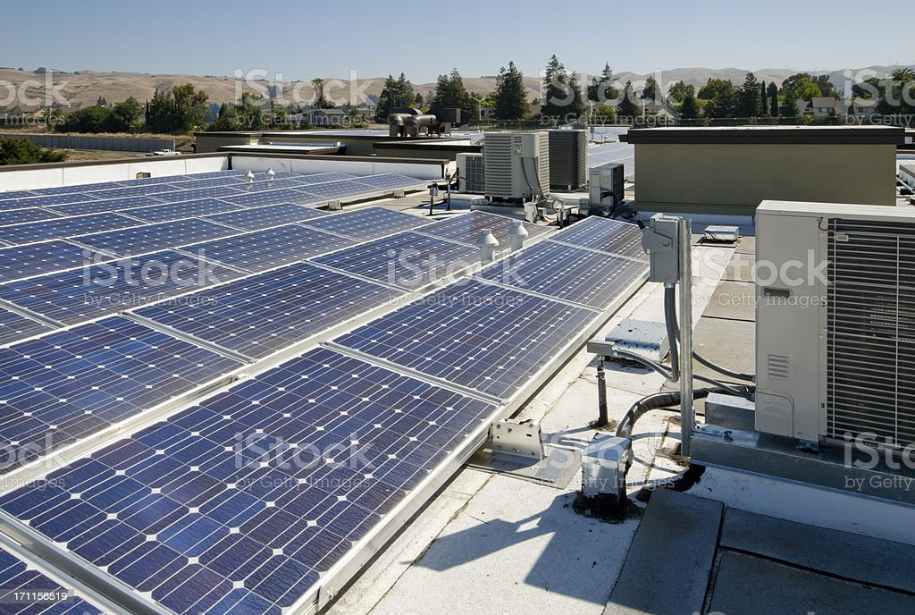 Solar panels gathering sunlight on a rooftop royalty-free stock photo