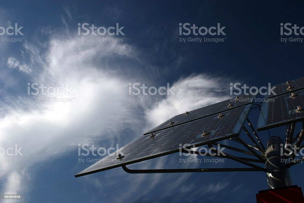 Solar panels in front of bizarre cirrus clouds stock photo