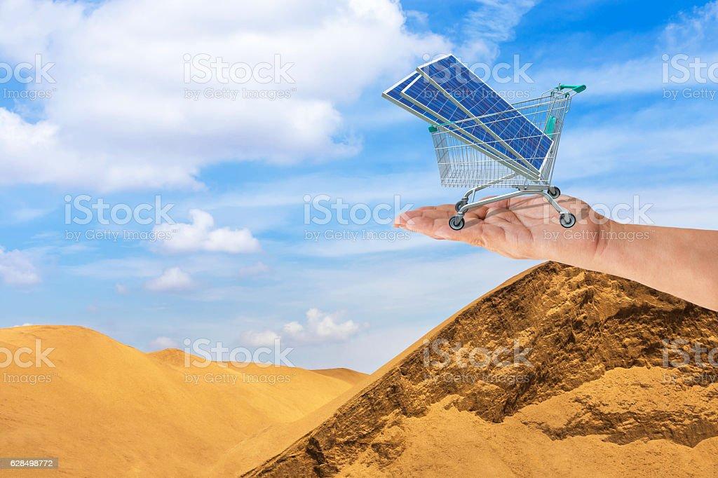 solar panels in shopping trolley cart on hand in desert. stock photo