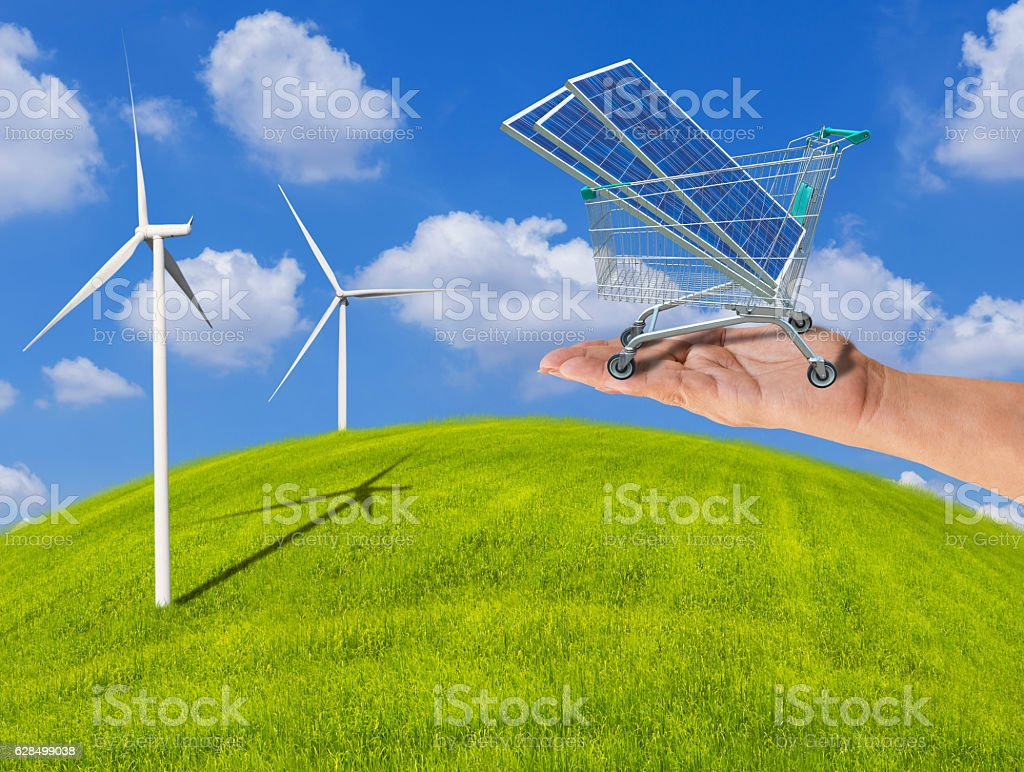 solar panels in trolley cart on hand with wind turbines stock photo
