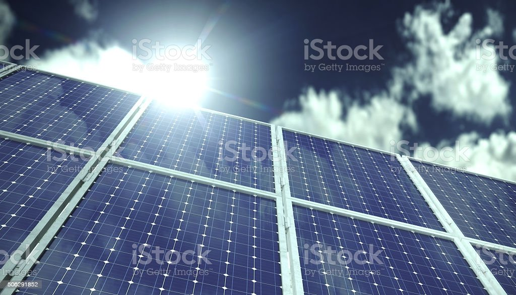 Solar panels infront of blue sky with clouds in sunlight stock photo