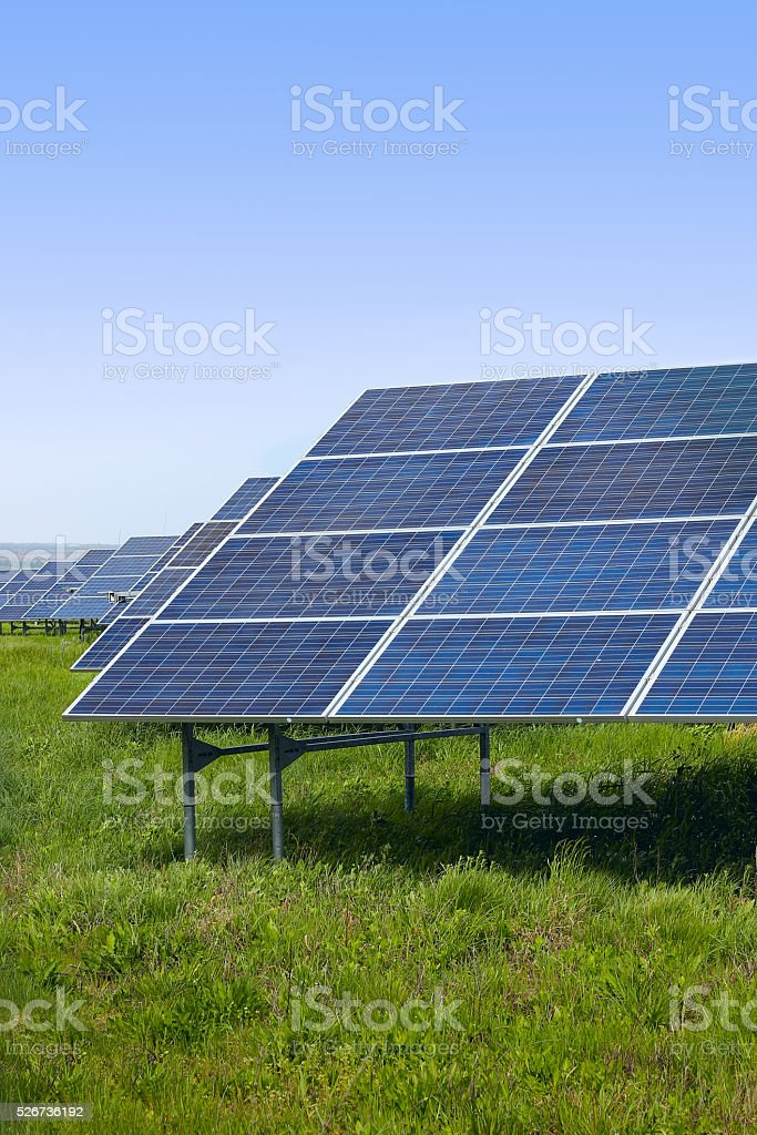 Solar panels on a green field on a sunny day stock photo