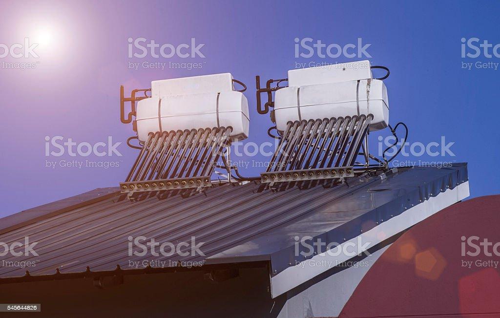 Solar panels on a roof under the blazing sun stock photo