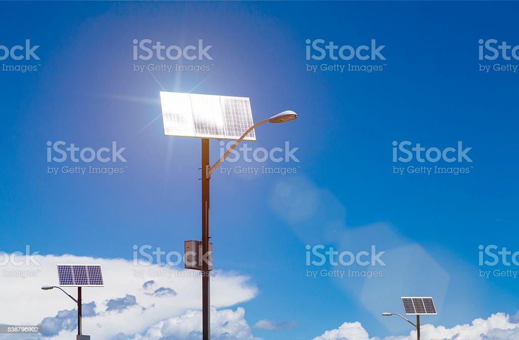 Solar panels on lampposts reflecting sunlight generating electric energy stock photo