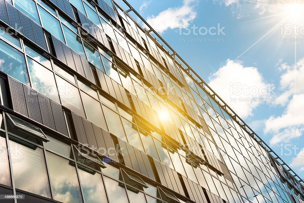 solar panels on modern glass facade with sun reflections stock photo