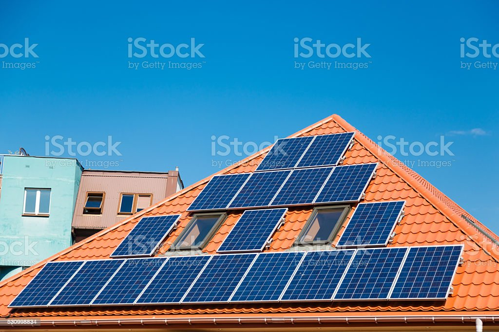 Solar panels on the red roof of a building stock photo