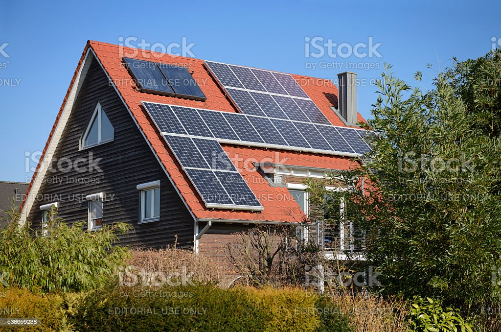 Solar panels on the roof of a generic one-family house stock photo