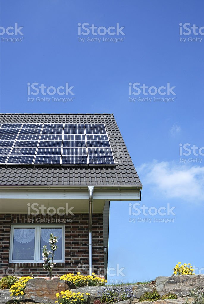 Solar panels on top of a brick house roof  stock photo