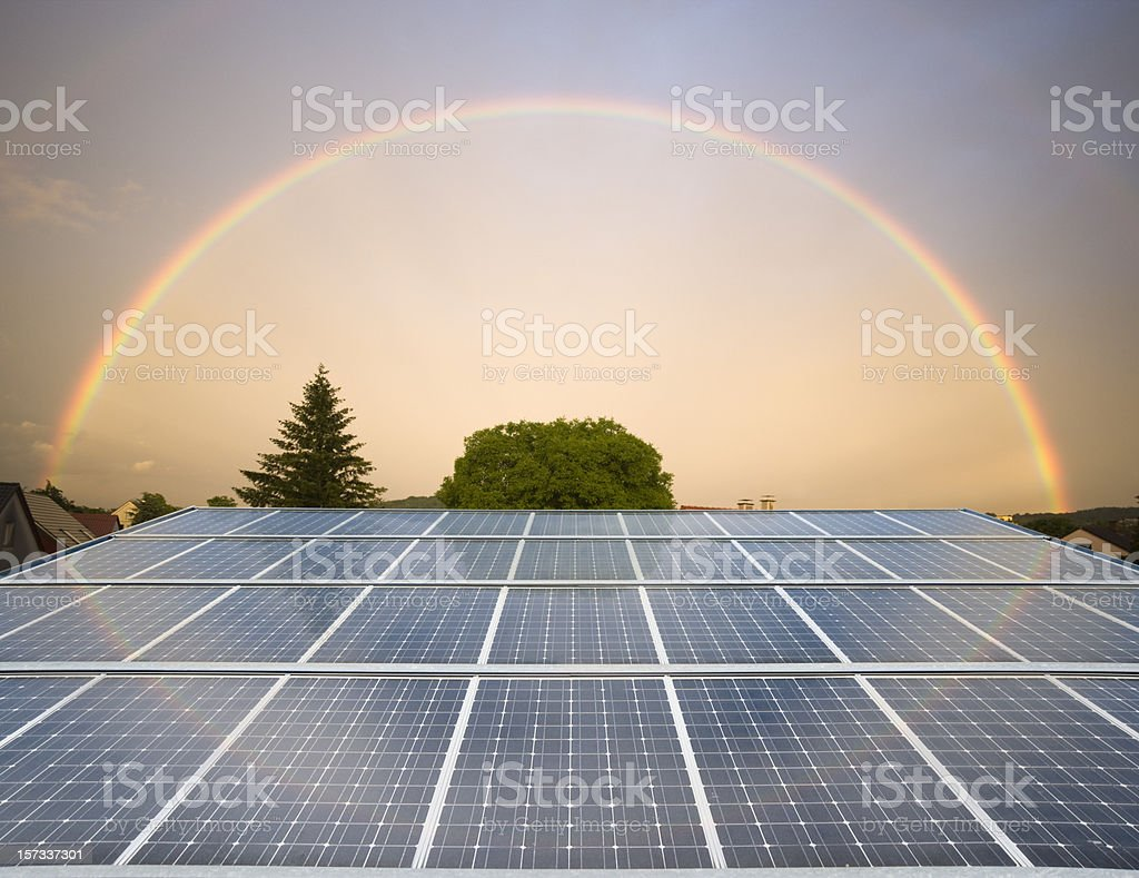 Solar panels with a rainbow in the sky stock photo