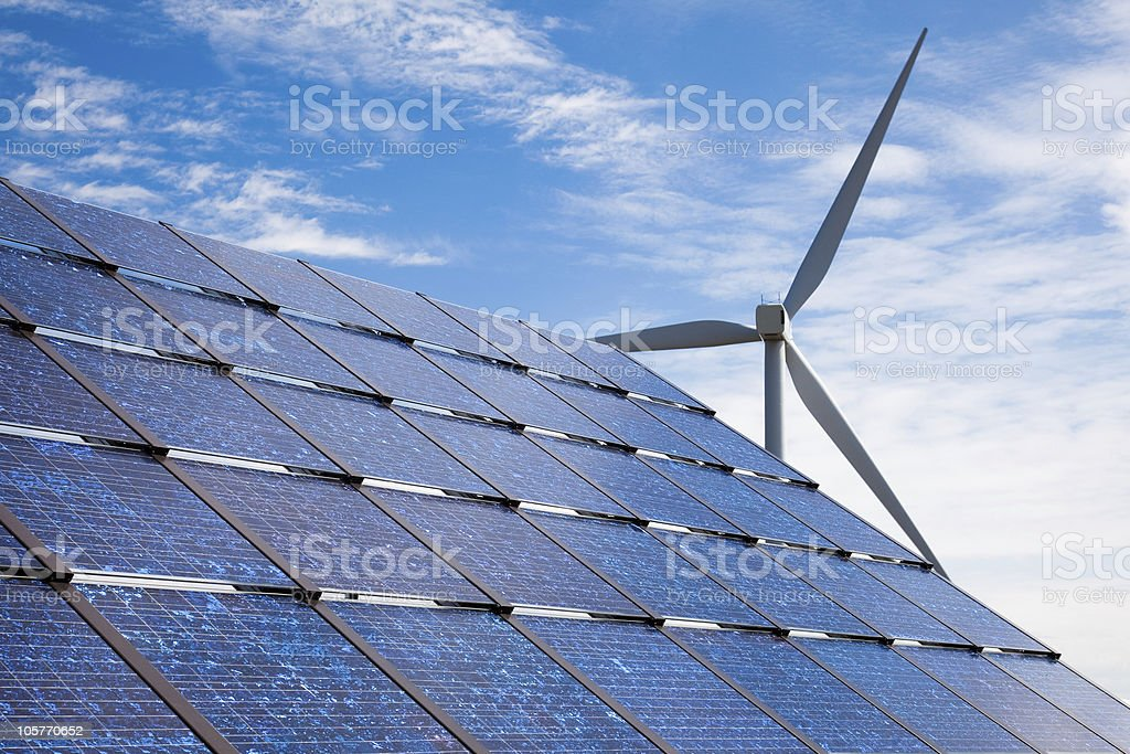 solar panels with wind turbine in the background stock photo