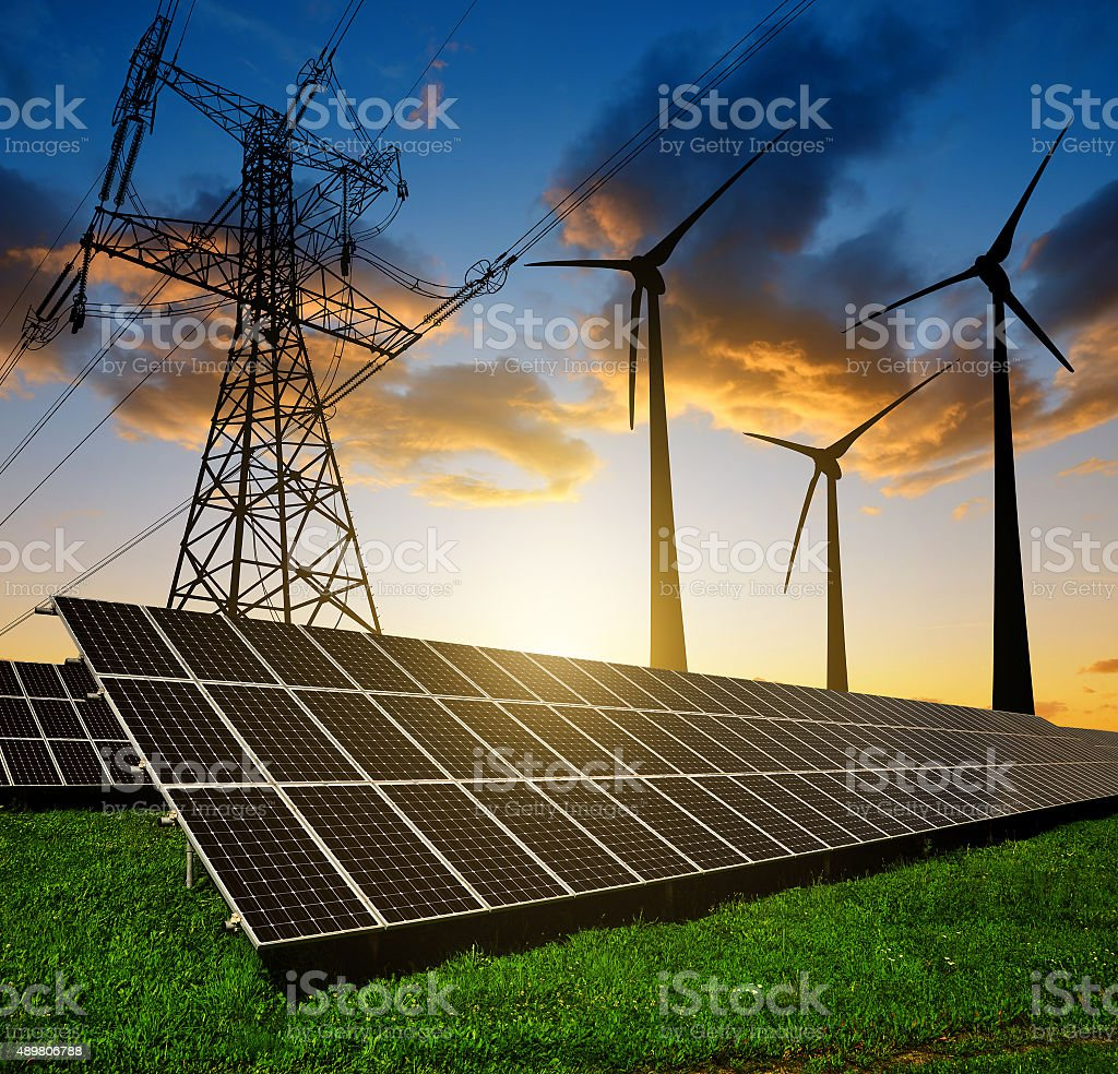 Solar panels with wind turbines and electricity pylon at sunset. stock photo