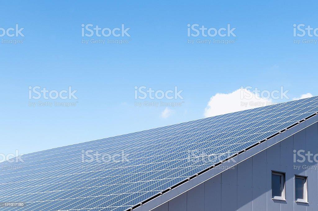Solar photovoltaic panel on an roof against a blue sky stock photo