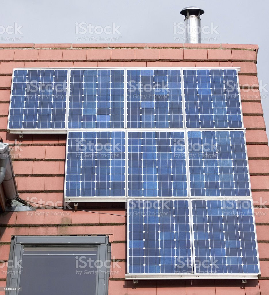 Solar photovoltaic panels on tiled house roof royalty-free stock photo