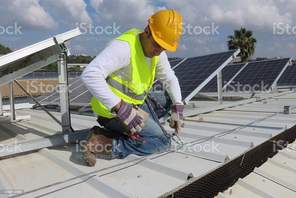 Solar Safety -Worker tying himself stock photo