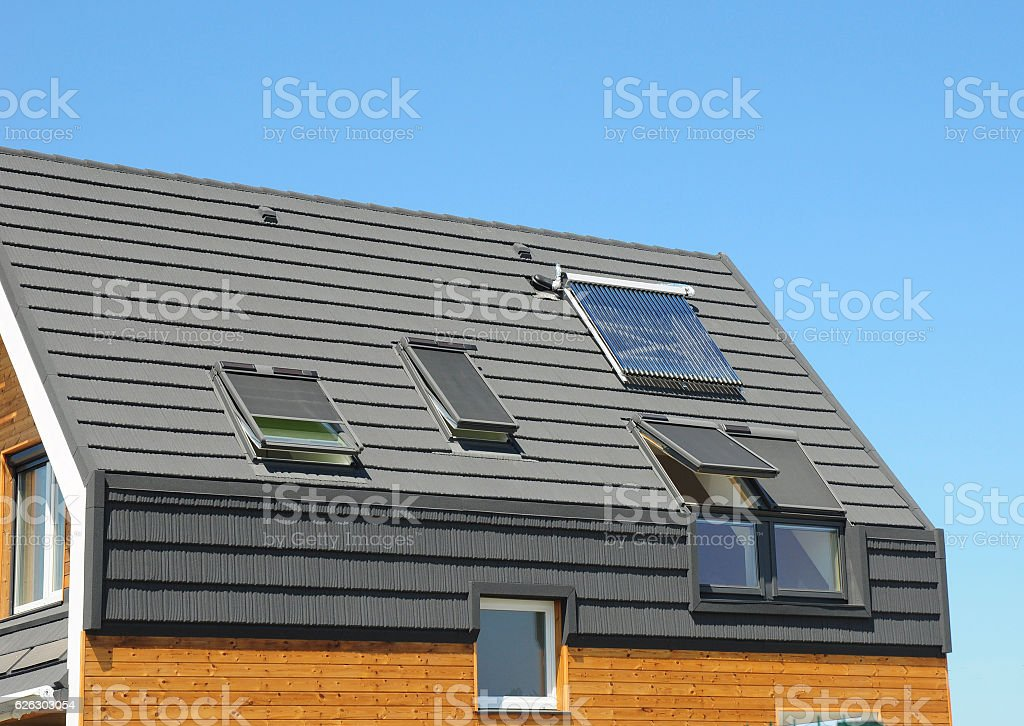 Solar water heater with skylights. Modern house roof. stock photo
