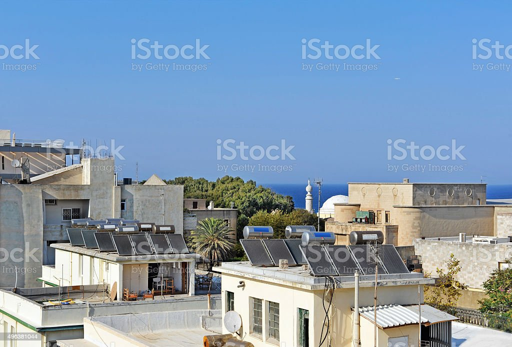 Solar water heating systems on the house's roofs stock photo