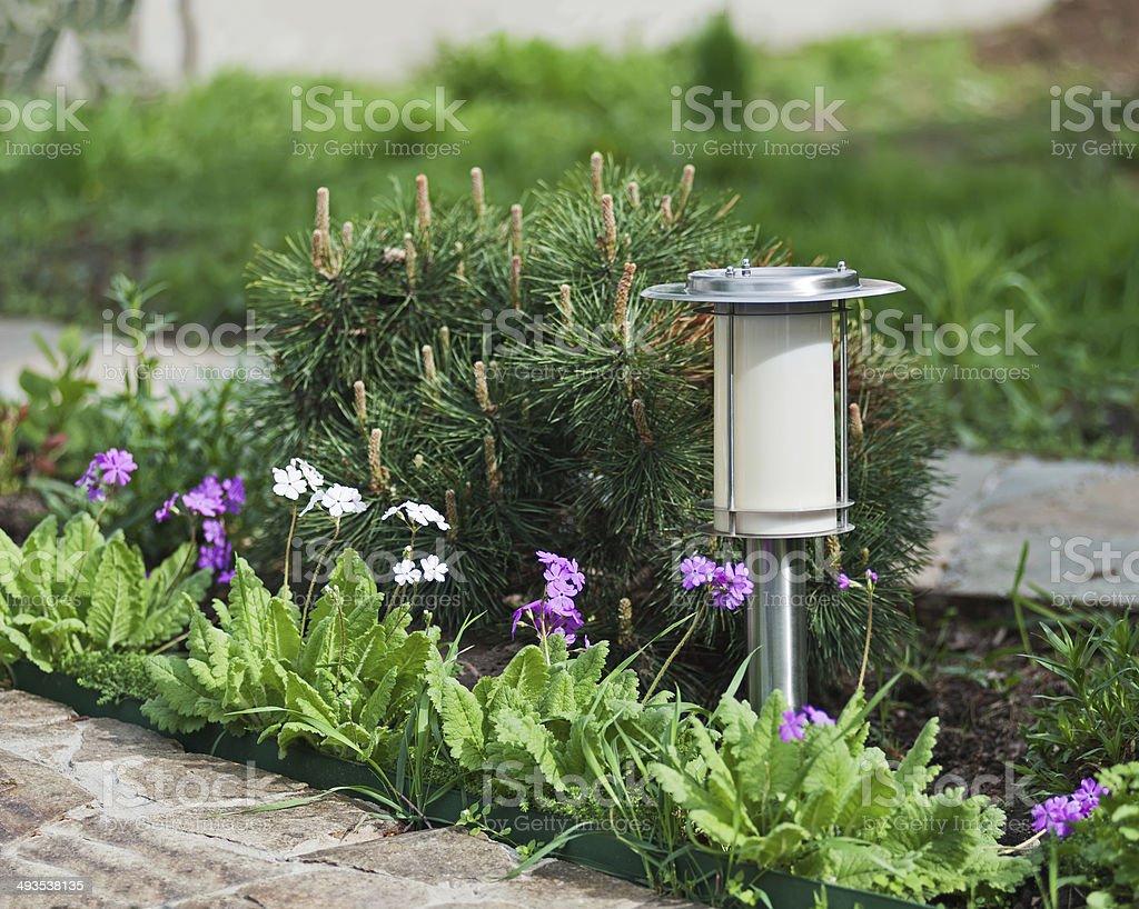 Solar-powered lamp on garden background. stock photo