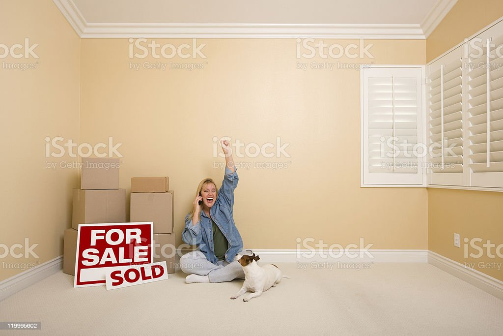 Sold Real Estate Signs, Boxes and Happy Woman on Phone royalty-free stock photo